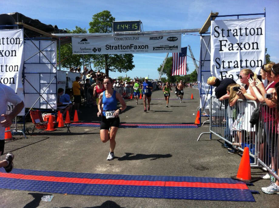 A runner crosses the Jennings Beach finish line Sunday morning the Stratton Faxon Fairfield Road Races. Photo: B.K. Angeletti / Fairfield Citizen contributed