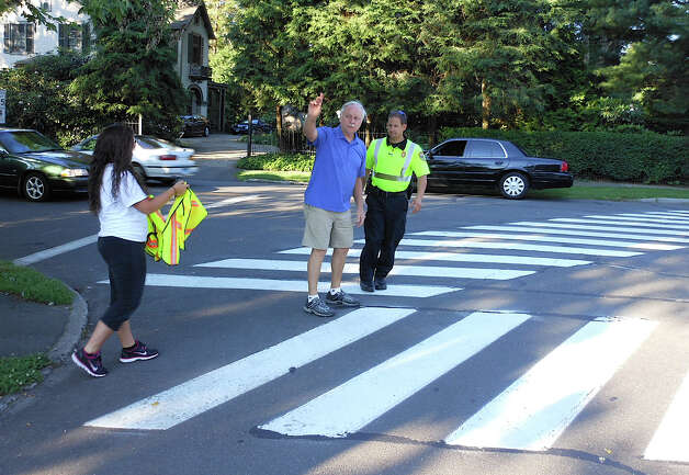 Fairfield Half Marathon race director Steve Lobdell guides a police officer at the corner of South Benson and Old Post roads on redirecting traffic flow around the race route early Sunday. Photo: Mike Lauterborn / Fairfield Citizen contributed