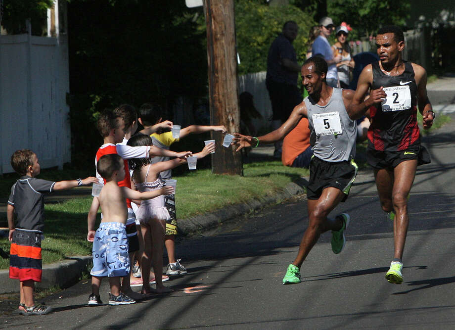 Tesfaye Girma, 5, of Ethiopia, takes water along the route of the annual Stratton Faxon Fairfield Half Marathon in Fairfield, Conn. on Sunday, June, 24, 2012. Photo: B.K. Angeletti / Connecticut Post