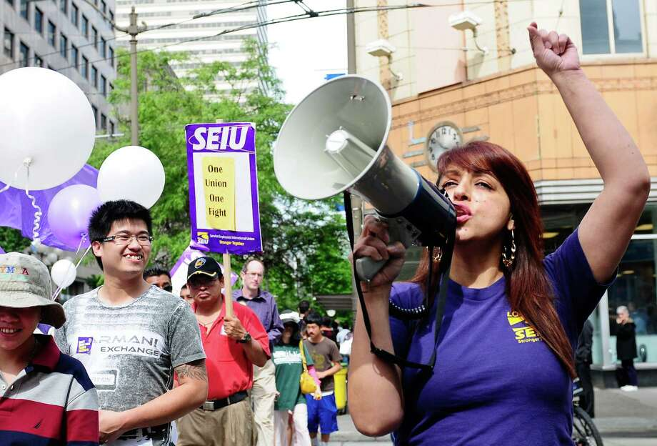 A volunteer encourages the crowd as they cross the street during the 22nd annual Justice for Janitors Day march in Seattle on Friday, June 15, 2012. The event began at Westlake with speeches and included a march through downtown Seattle, which stopped at various businesses like Russell Investment Center to protest unfair treatment of workers.  The SEIU Local 6 organized the event and represents professions such as airport workers, janitors, security officers and custodial workers. Photo: LINDSEY WASSON / SEATTLEPI.COM