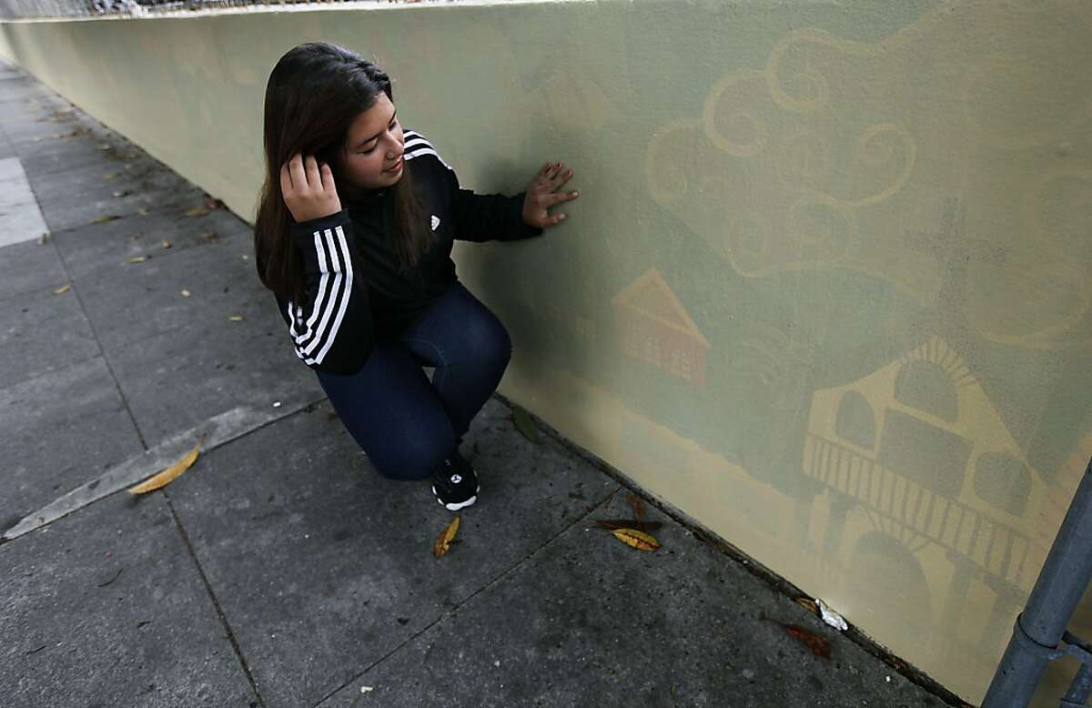 Tiffani Castro views what's left of the mural at Buena Vista/Horace Mann School in San Francisco on Friday.