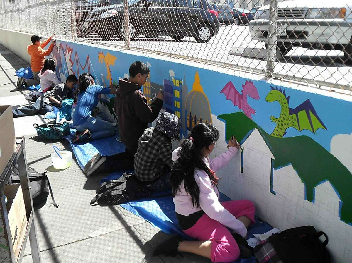 Students at Buena Vista Horace Mann K-8 school in San Francisco paint the first part of a mural along the Bartlett Street wall in 2011.