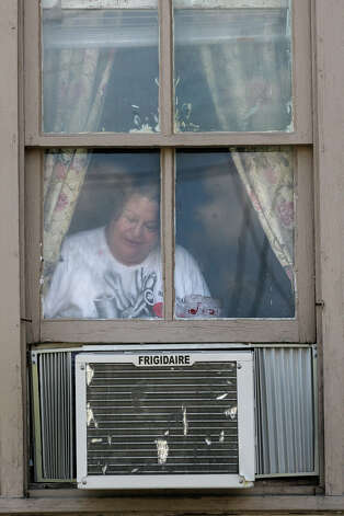 Maria Reitzer adjust her window air conditioner as the temperature rises throughout South Texas, Sunday, June 24, 2012. Reitzer and her daughter were adjusting the unit because it wasn't cooling properly. She was at her house near the corner of North Las Moras Street and West Houston Street. Photo: Jerry Lara, San Antonio Express-News / © 2012 San Antonio Express-News