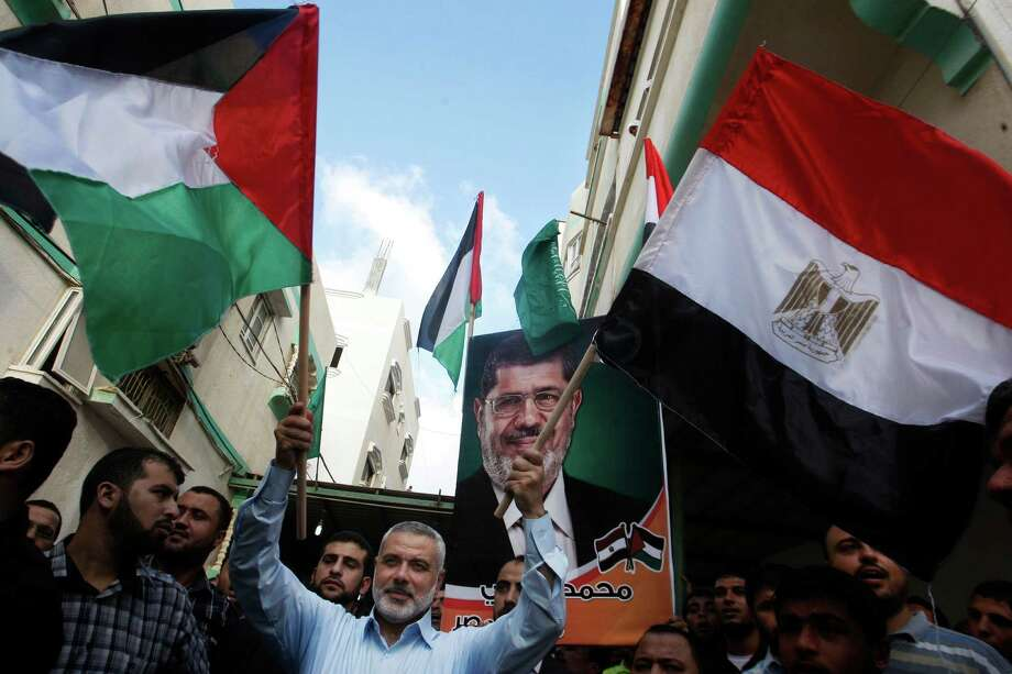 Gaza's Hamas Prime Minister Ismail Haniyeh, center, waves the Palestinian and Egyptian flags during celebrations of the victory of Mohammed Morsi in the Egyptian presidential elections, in Gaza City, Sunday, June 24, 2012. The Muslim Brotherhood victory in Egyptian presidential elections raises fears in Israel that the historic 1979 peace agreement with its southern neighbor is now in danger, a scenario that would have grave implications for regional security. But in the Hamas-ruled Gaza Strip, ecstatic residents flock to the streets, fire guns into the air and distribute candies in celebration, hopeful that Mohammed Morsi's election will usher in a new era for the blockaded seaside territory. (AP Photo/Hatem Moussa) Photo: Hatem Moussa / AP