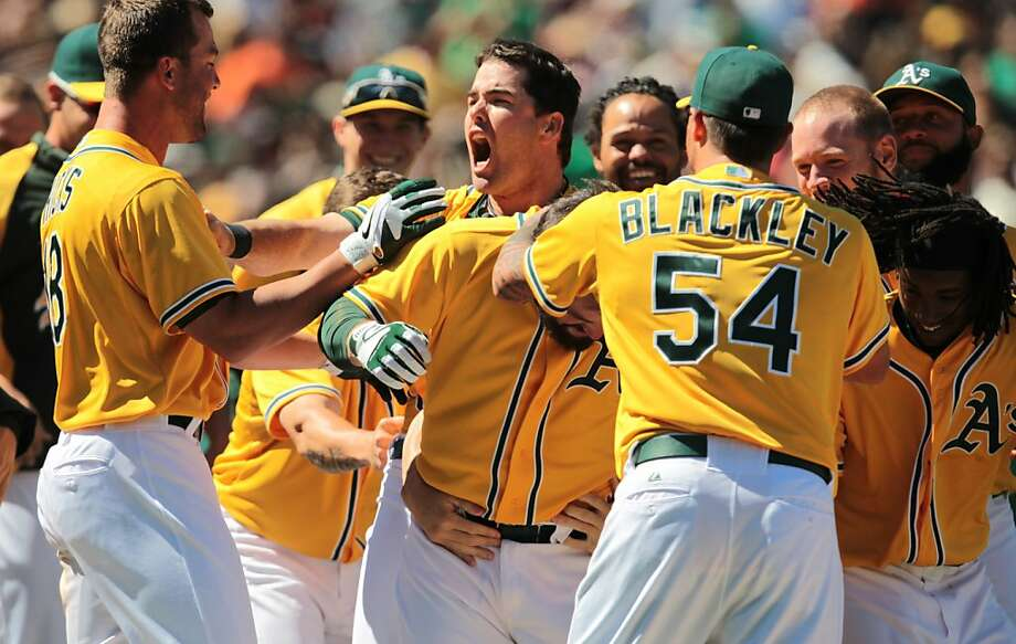 The Athletics' Seth Smith, center, Travis Blackley and other teammates celebrate catcher Derek Norris' three-run walk off homer to beat the Giants 4-2 at the Coliseum in Oakland, Calif. on Sunday, June 24, 2012. Photo: Mathew Sumner, Special To The Chronicle