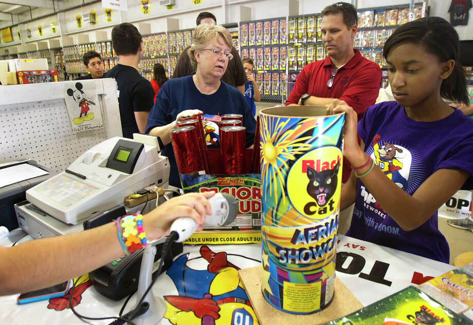 Workers Sue Davis, left, and Ashley Isles check out purchases by Lou Cooper, center, after he makes his selections at Top Dog Fireworks on Sunday. Photo: Cody Duty / © 2011 Houston Chronicle