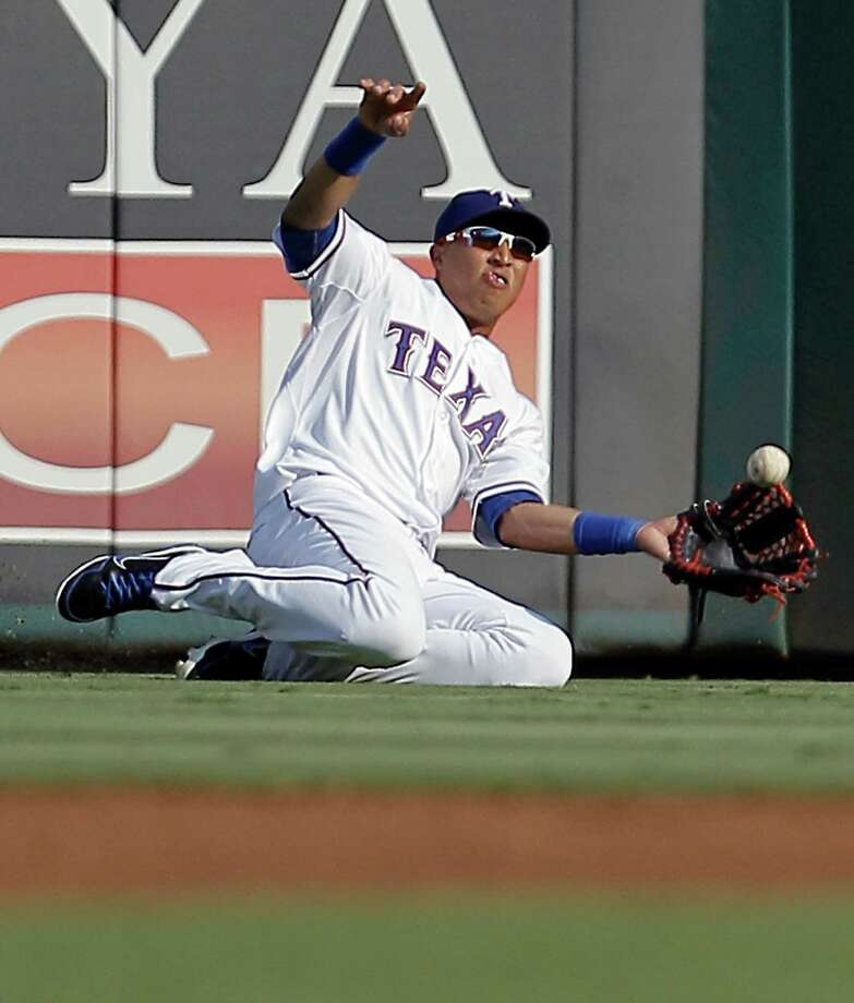 Texas Rangers center fielder Leonys Martin (27) tries to catch a ball hit by Colorado Rockies' Marco Scutaro during the first inning of an interleague baseball game in Arlington, Texas, Sunday, June 24, 2012. Martin was unable to come up with the catch. Photo: AP