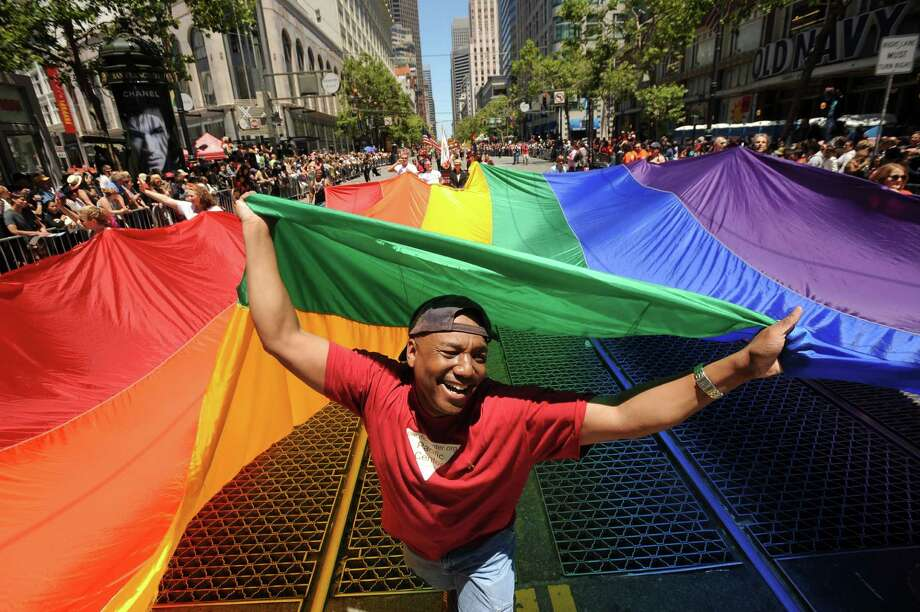 Mark Wilson carries a rainbow flag during San Francisco's 42nd annual gay pride parade on Sunday, June 24, 2012. Organizers say more than 200 floats, vehicles and groups of marchers took part in the parade. Photo: Noah Berger, Associated Press / FR34727 AP