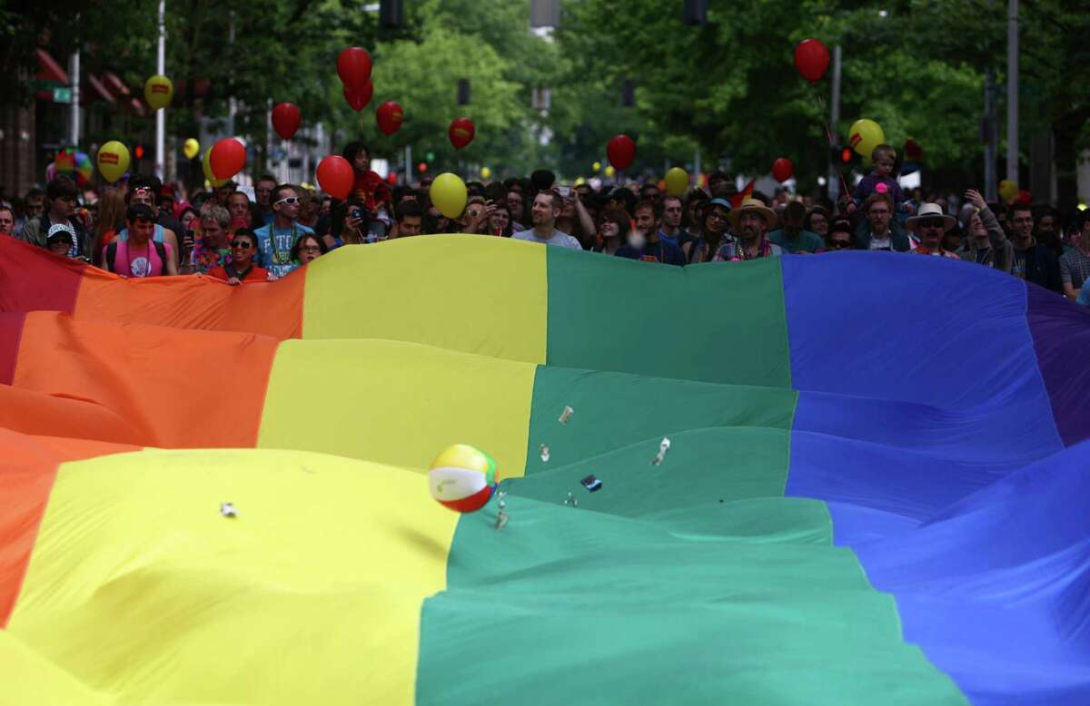 People march behind a giant pride flag.