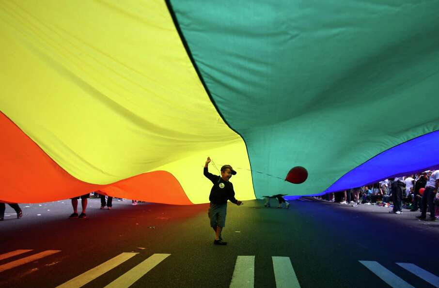 A young parade spectator ends up under a giant pride flag  during Seattle's annual Pride Parade on S
