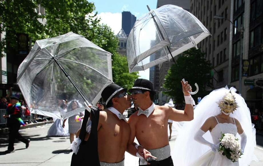 Luis Aguilar, left, kisses his partner Luis Fernando as they march. Photo: JOSHUA TRUJILLO / SEATTLEPI.COM