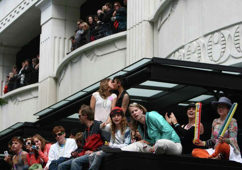 People watch from the roof of a bus shelter.