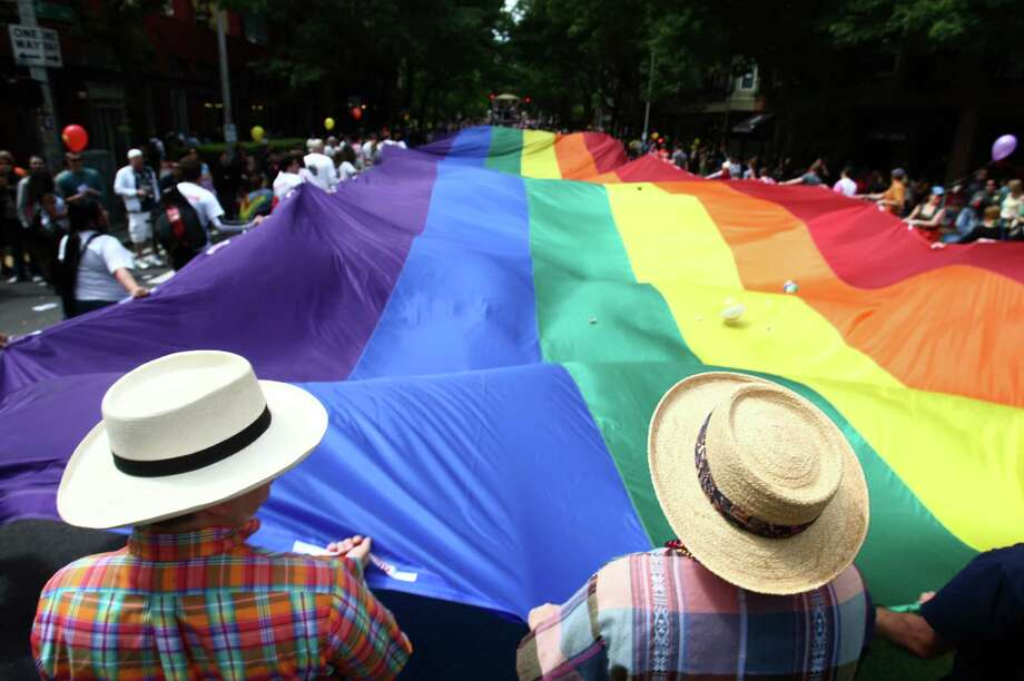 Parade participants wave a large pride flag. Photo: JOSHUA TRUJILLO / SEATTLEPI.COM