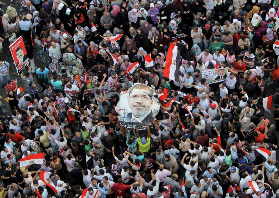 Egyptians carry a poster of newly elected President Mohammed Morsi in Cairo's Tahrir Square, the epicenter of the protests that led to Hosni Mubarak's ouster. Photo: Amr Nabil / AP