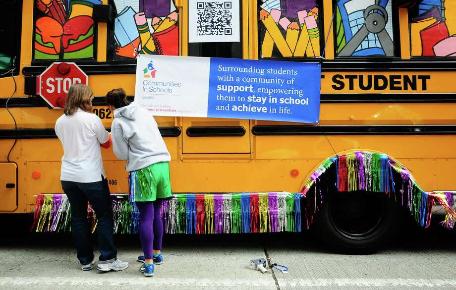 Shira Rosen, left, and Danika Martinez, right, secure the Communities in Schools banner to a school bus before the parade. Photo: LINDSEY WASSON / SEATTLEPI.COM