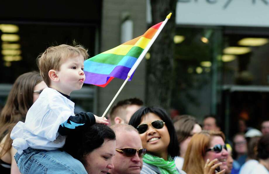 A young boy holds a rainbow flag as he rides on a woman's shoulders. Photo: LINDSEY WASSON / SEATTLEPI.COM