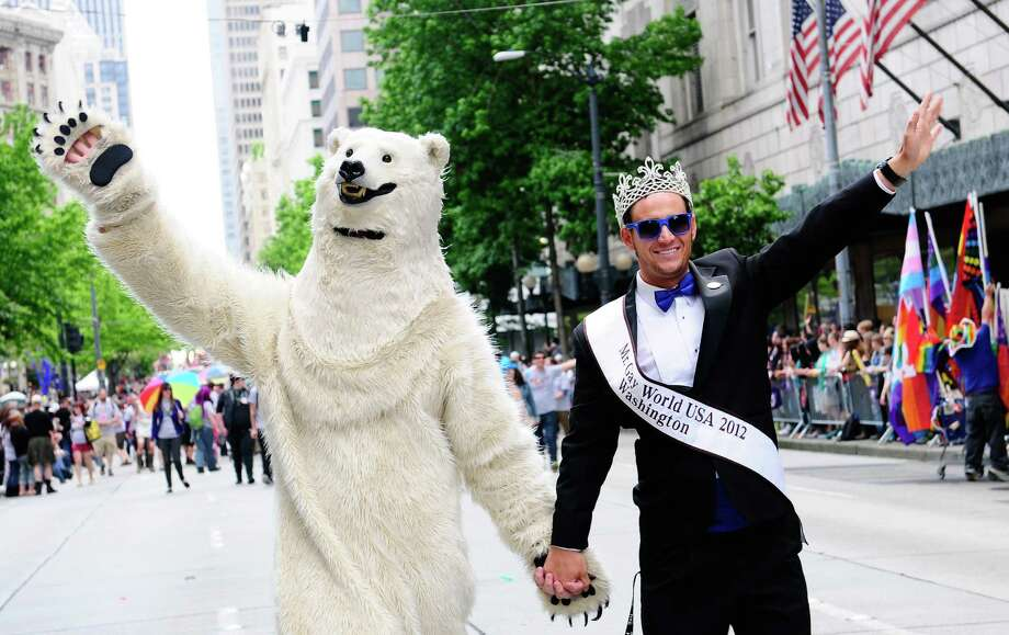Mr. Gay World USA 2012 and a polar bear wave to the crowd. Photo: LINDSEY WASSON / SEATTLEPI.COM