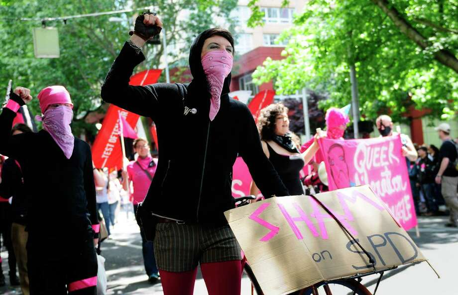 A protester of the Seattle Police Department raises her fist as she walks. Photo: LINDSEY WASSON / SEATTLEPI.COM