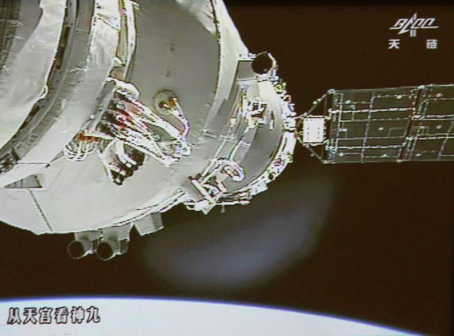 In this image made off the screen at the Beijing Aerospace Control Center in Beijing and released by China's Xinhua News Agency, Shenzhou-9 spacecraft and Tiangong-1 lab module, partly seen on left, are conjoined again Sunday, June 24, 2012. Three Chinese astronauts Sunday successfully completed a manual docking between of the spacecraft and the orbiting module, the first such attempt in China's history of space exploration. (AP Photo/Beijing Aerospace Control Center via Xinhua)
