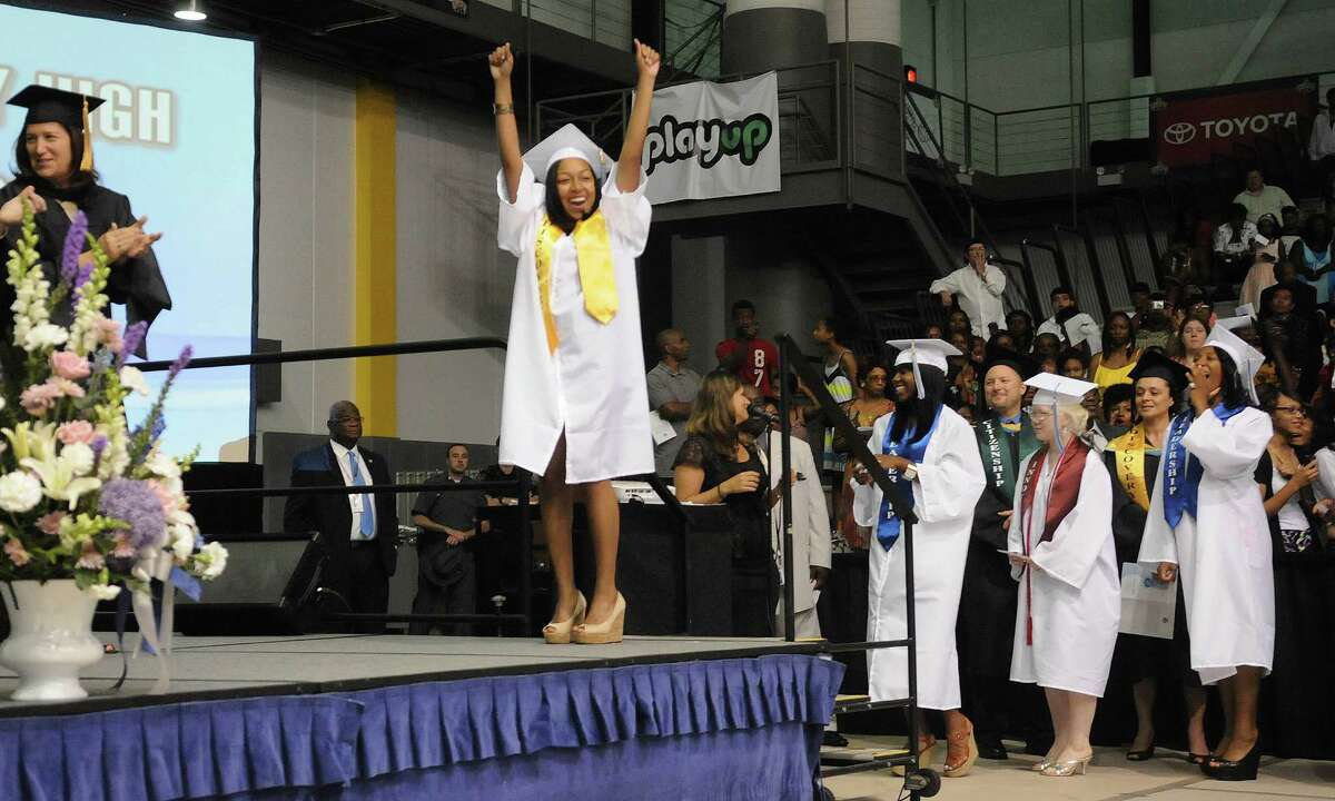 Graduate Katherine Boyd raises her arms as she walks on stage to receive her diploma during the Albany High School graduation at the SEFCU Arena on the campus of the University at Albany on Sunday, June 24, 2012 in Albany, NY. (Paul Buckowski / Times Union)