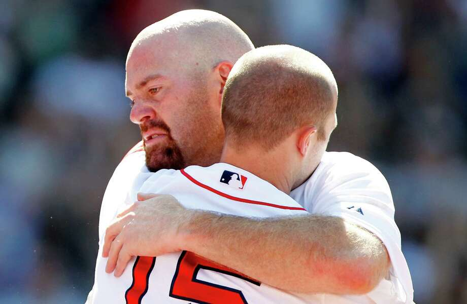 After tripling in his final at-bat for the Red Sox, Kevin Youkilis, left, bids farewell to Fenway with a hug from Dustin Pedroia and a standing ovation from the crowd after being lifted for a pinch runner. Hours later, a trade of Youkilis to the White Sox for righthander Zach Stewart and utility player Brent Lillibridge became official. Photo: Michael Dwyer / AP