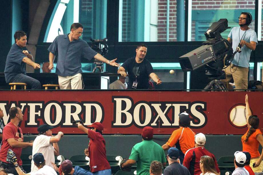 Fans and members of the TV crew unite in their desire to grab a home run ball hit by J.D. Martinez that completed the scoring in the eighth inning and gave the Astros their first back-to-back games with seven or more runs of the season. Photo: Michael Paulsen / © 2012 Houston Chronicle