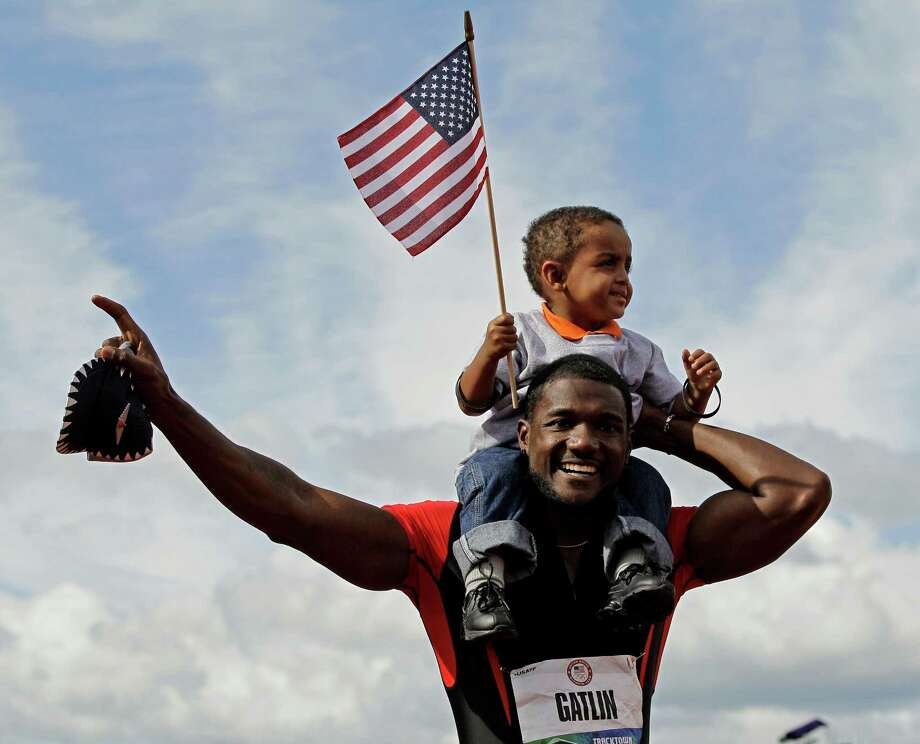 Justin Gatlin reacts with his son Jace after winning the men's 100m finals at the U.S. Olympic Track and Field Trials Sunday, June 24, 2012, in Eugene, Ore. (AP Photo/Eric Gay) Photo: Associated Press