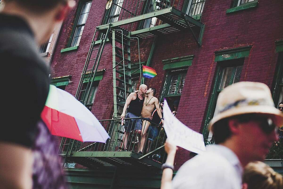 NEW YORK - JUNE 24: Revelers kiss on a fire escape during the New York City Gay Pride March on June 24, 2012 in New York City. The annual civil rights demonstration commemorates the Stonewall riots of 1969, which erupted after a police raid on a gay bar, the Stonewall Inn on Christopher Street. (Photo by Michael Nagle/Getty Images)