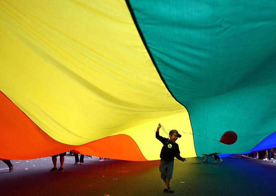 A child holds a balloon under a Pride flag held by participants marching during Seattle's annual Gay Pride Parade on Sunday, June 24, 2012. (AP Photo/seattlepi.com, Joshua Trujillo) Photo: Joshua Trujillo, Associated Press