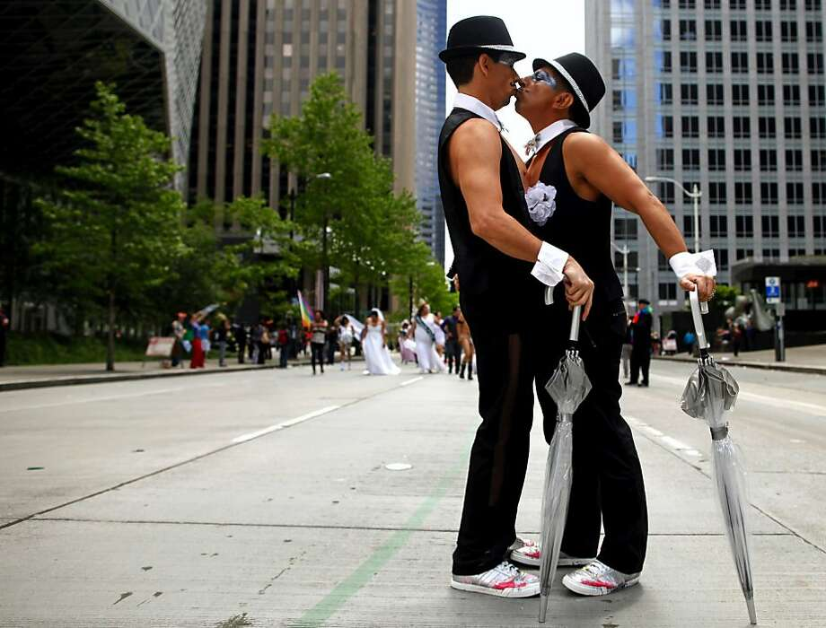 "Luis Ramirez, left, and Luis Aguilar share a kiss during the Seattle Gay Pride Parade on Sunday, June 24, 2012, in Seattle. The couple walked with ""Entre Hermanos,"" a Seattle Latino LGBT organization, and dressed in wedding-themed attire to promote marriage equality. (AP Photo/The Seattle Times, Erika Schultz) SEATTLE OUT; USA TODAY OUT; MAGS OUT; TV OUT; SALES OUT; MANDATORY CREDIT Photo: Erika Schultz, Associated Press"