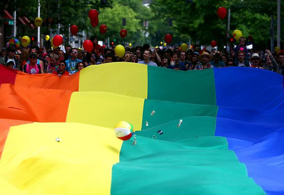 Participants march with a Pride flag during Seattle's annual Gay Pride Parade on Sunday, June 24, 2012. (AP Photo/seattlepi.com, Joshua Trujillo) Photo: Joshua Trujillo, Associated Press