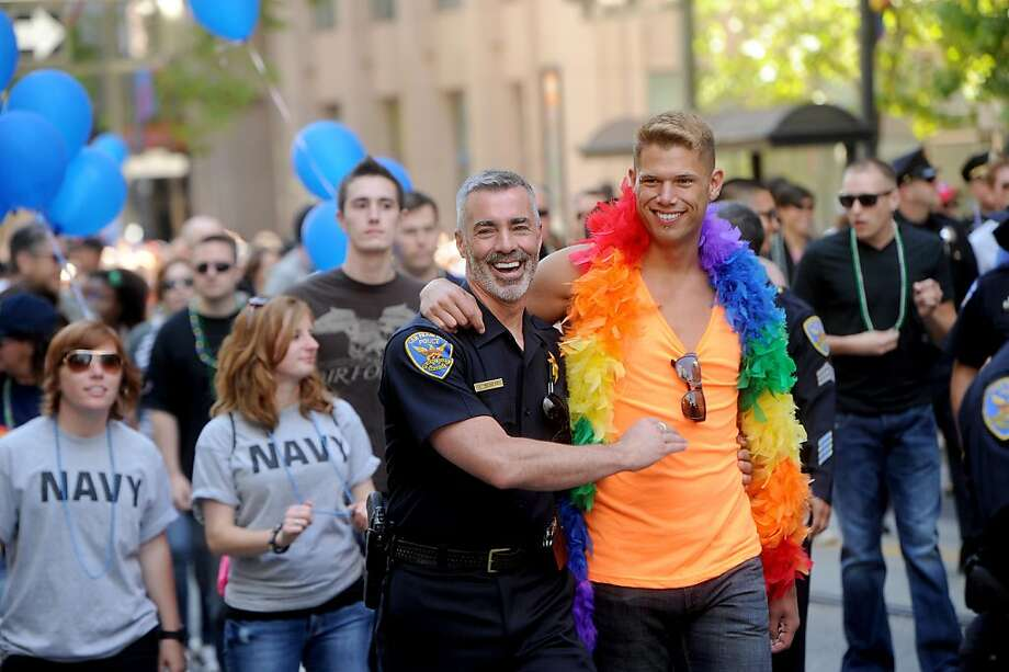Lenny Broberg, an inspector with the San Francisco police department, hugs boyfriend Eric Kissenger while marching in San Francisco's 42nd annual gay pride parade on Sunday, June 24, 2012.  Organizers say more than 200 floats, vehicles and groups of marchers took part in the parade. (AP Photo/Noah Berger) Photo: Noah Berger, Associated Press