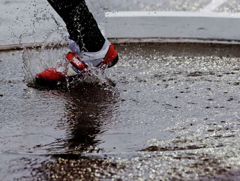 An athlete throws a shot put from a puddle during a downpour at the U.S. Olympic Track and Field Tri