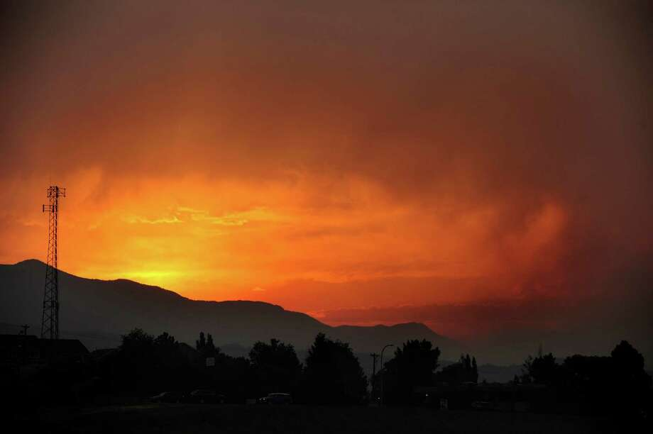 The sun sets as seen from Lower Gold Camp Road as a wildfire continues to burn west of Colorado Springs, Colo. on Sunday, June 24, 2012. The fire erupted Saturday and grew out of control to more than 3 square miles early Sunday, prompting the evacuation of more than 11,000 residents and an unknown number of tourists. Photo: The Colorado Springs Gazette, Susannah Kay