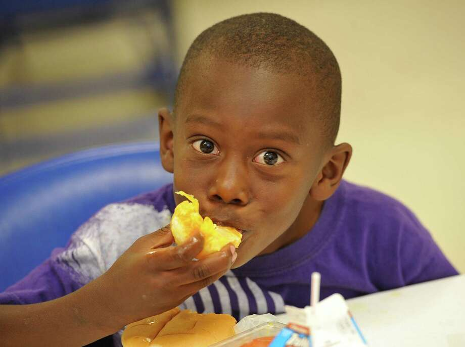 Trovoris Zeno takes a bite of his orange with his turkey and cheese sandwich Tuesday June 19, 2012.   Beaumont ISD is starting their summer feeding programs this year with 13 schools participating as well as other community spots to which they provide food. It's always a challenge for school districts to find the right spot to get the maximum amount kids to go to their feeding program, so they're not wasting food. Some area districts have consolidated their summer feeding program and have shortened the feeding schedule. Other area programs then take over. At the Jefferson County Commissioner Bo Alfred's precinct 4 building on Boyt Road, they go a bit further with their lunch program by adding a guest speaker or a demonstration, something that is interesting to the kids.  Dave Ryan/The Enterprise