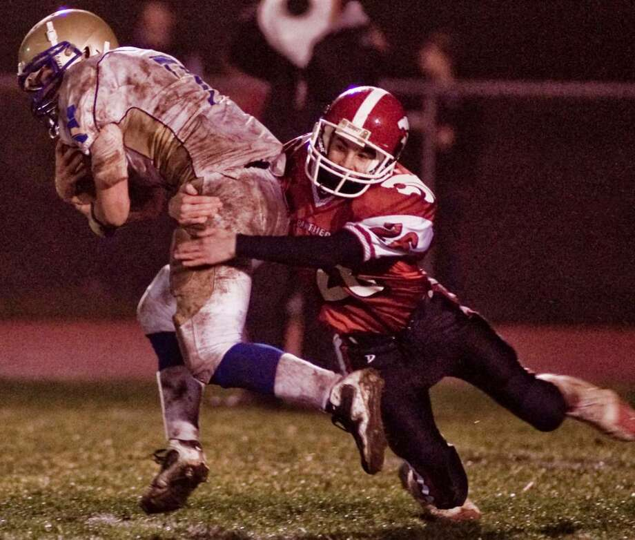 Newtown senior Kyle O'Connor tries to escape a tackle by Masuk junior Lenny Bonina during football game at Masuk. Wednesday, Nov. 25 2009 Photo: Scott Mullin / The News-Times