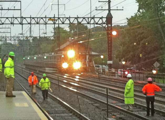 Train traffic through the Southport Railroad Station was reduced to a single eastbound track Monday morning after lightning struck an overhead catenary structure, causing a power line to fall. Here, Metro-North Railroad officials assess the damge. Photo: Genevieve Reilly / Fairfield Citizen