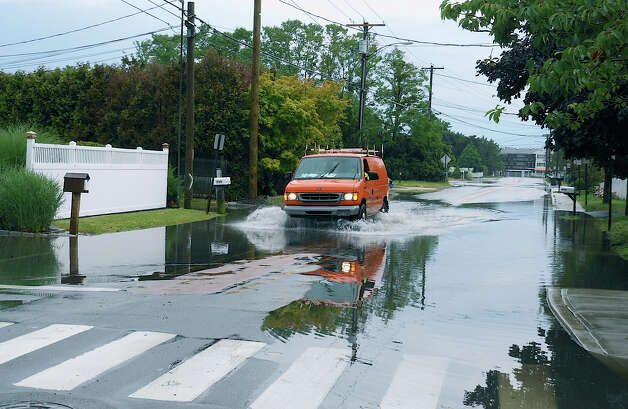 A van plows through collected storm water along Fairfield Beach Road in the wake of Monday morning powerful thunderstorm. Photo: Mike Lauterborn / Fairfield Citizen contributed