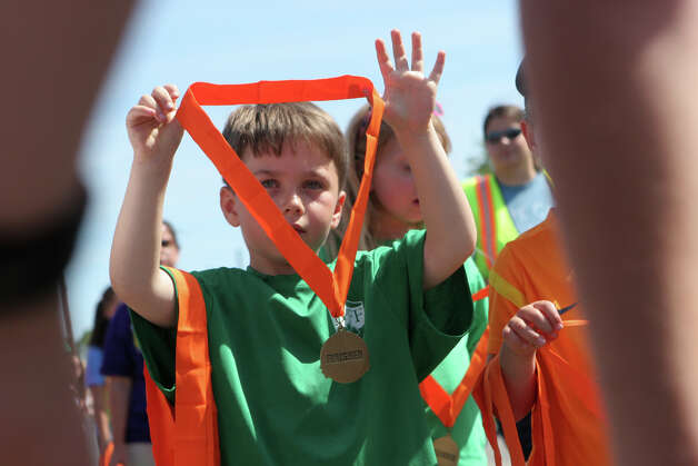 Jack Flanagan,6, of Fairfield, hands out medals at  the annual Stratton Faxon Fairfield Half Marathon in Fairfield, Conn. on Sunday, June, 24, 2012. Photo: B.K. Angeletti / Connecticut Post