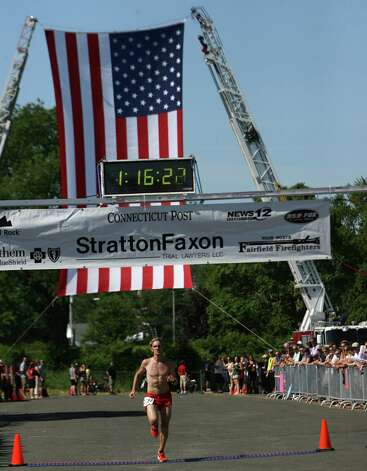 Luke McCambley, of Westport, crosses the finish line of the annual Stratton Faxon Fairfield Half Marathon in Fairfield, Conn. on Sunday, June, 24, 2012. Photo: B.K. Angeletti / Connecticut Post