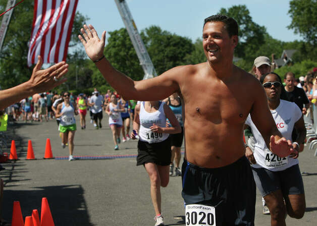 Mark Gentilozzi, of Fairfield, gets a high five at the finish line of the annual Stratton Faxon Fairfield Half Marathon in Fairfield, Conn. on Sunday, June, 24, 2012. Photo: B.K. Angeletti / Connecticut Post