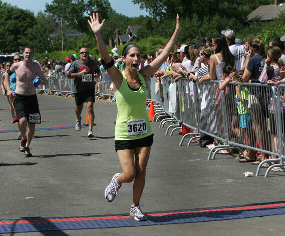 Laurie McAnaspie, of Danbury, celebrates at the finish line of the annual Stratton Faxon Fairfield Half Marathon in Fairfield, Conn. on Sunday, June, 24, 2012. Photo: B.K. Angeletti / Connecticut Post