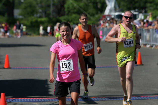 Caitlin Stote, of Stamford, of Stamford, crosses the finish line of the annual Stratton Faxon Fairfield Half Marathon in Fairfield, Conn. on Sunday, June, 24, 2012. Stote took second for Conn. women and first for women 20-29 years,. Photo: B.K. Angeletti / Connecticut Post