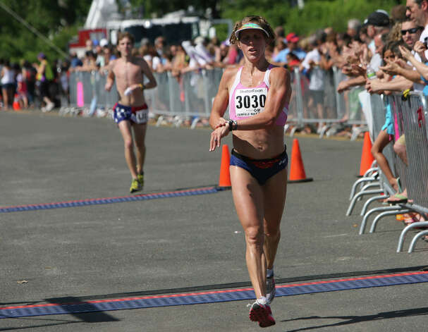Amy Bevilacqua, of Wilton, crosses the finish line of the annual Stratton Faxon Fairfield Half Marathon in Fairfield, Conn. on Sunday, June, 24, 2012. Photo: B.K. Angeletti / Connecticut Post