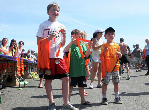 Volunteers from, left, Mike Costello, 11, Jack Flanagan, 5, and Nathan Frey, 5, all of Fairfield, hand out medals the annual Stratton Faxon Fairfield Half Marathon in Fairfield, Conn. on Sunday, June, 24, 2012. Photo: B.K. Angeletti / Connecticut Post