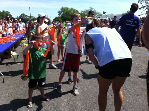 Runners at the finish line of Sunday's Fairfield Half Marathon get medals in recognition of the achievement of finishing the 13.1-mile course. Photo: B.K. Angeletti / Fairfield Citizen contributed