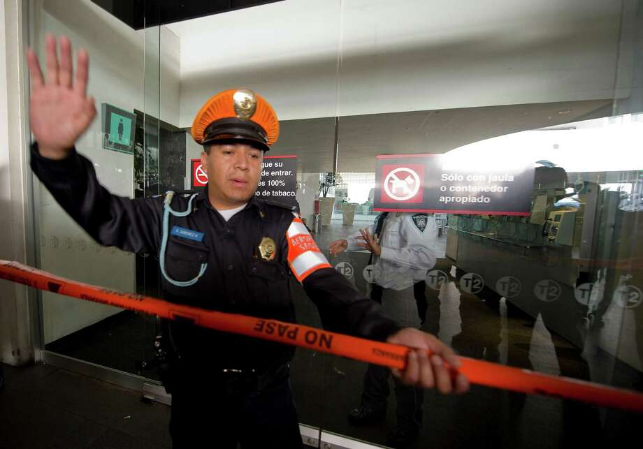 A police officer cordon's off an entrance near the fast-food area of Benito Juarez international airport Terminal 2, in Mexico City where two police officers were shot dead and a third was wounded on June 25, 2012. Airport spokesman Jorge Andres Gomez said authorities are going through the security cameras to know the exact events of the shooting.   AFP PHOTO/Alfredo ESTRELLAALFREDO ESTRELLA/AFP/GettyImages Photo: ALFREDO ESTRELLA, AFP/Getty Images / AFP