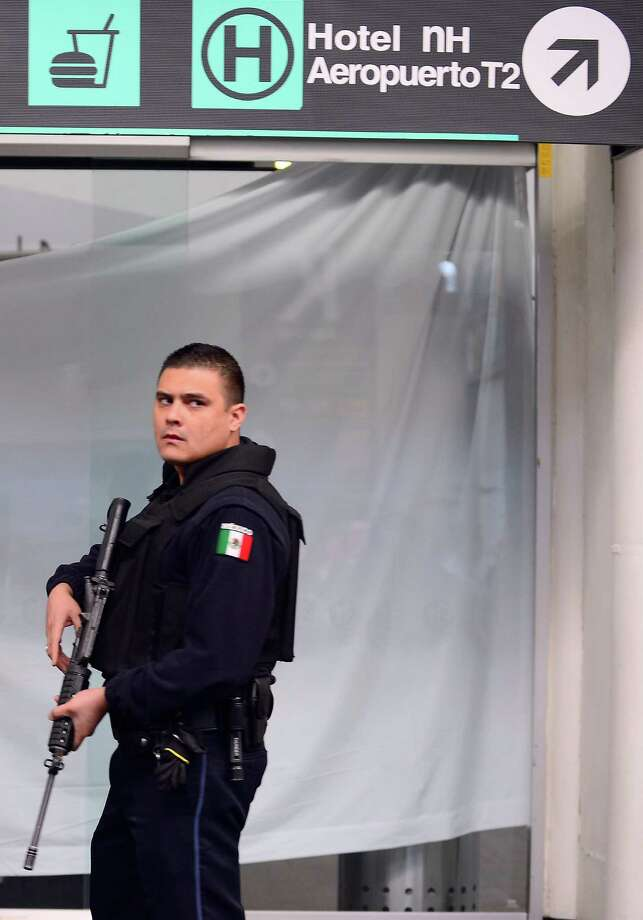 A Federal Police officer stands guard at an entrance near the fast-food area of Benito Juarez international airport Terminal 2, in Mexico City where two police officers were shot dead and a third was wounded on June 25, 2012. Airport spokesman Jorge Andres Gomez said authorities are going through the security cameras to know the exact events of the shooting.   AFP PHOTO/Alfredo ESTRELLAALFREDO ESTRELLA/AFP/GettyImages Photo: ALFREDO ESTRELLA, AFP/Getty Images / AFP