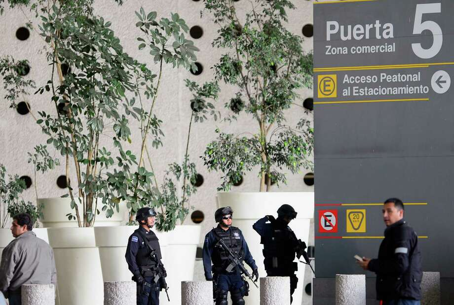 Federal Police officers stand guard at Benito Juarez international airport Terminal 2, in Mexico City, where, in the fast-food area, two police officers were shot dead and a third was wounded on June 25, 2012. Airport spokesman Jorge Andres Gomez said authorities are going through the security cameras to know the exact events of the shooting.   AFP PHOTO/Alfredo ESTRELLAALFREDO ESTRELLA/AFP/GettyImages Photo: ALFREDO ESTRELLA, AFP/Getty Images / AFP