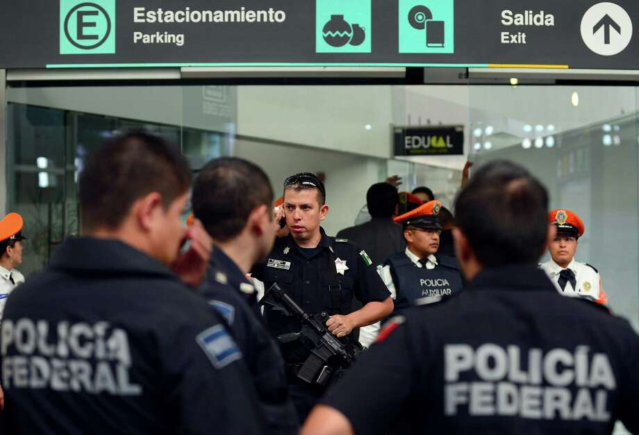 Federal Police officers stand guard near the fast-food area of Benito Juarez international airport Terminal 2, in Mexico City where two police officers were shot dead and a third was wounded on June 25, 2012. Airport spokesman Jorge Andres Gomez said authorities are going through the security cameras to know the exact events of the shooting.   AFP PHOTO/Alfredo ESTRELLAALFREDO ESTRELLA/AFP/GettyImages Photo: ALFREDO ESTRELLA, AFP/Getty Images / AFP